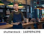 Successful small business owner using digital tablet and looking at camera. Happy smiling waiter ready to take order. Portrait of young entrepreneur of coffee shop standing at counter with copy space.