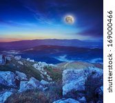 night mountain landscape with moon. valley with stones on the hillside. forest on the mountain under the beam of light falls on a clearing at the top of the hill. - stock photo