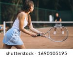 Young woman playing tennis at...