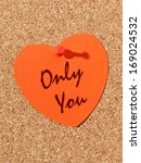 Red paper heart with Only You text pinned to the corkboard - stock photo