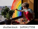 Small photo of let's all be well. child at home draws a rainbow on the window. Flash mob society community on self-isolation quarantine pandemic coronavirus. Children create artist paints creativity vacation