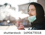 Small photo of Smoking. Closeup man with mask during COVID-19 pandemic smoking a cigarette at the street. Smoking causes lung cancer and other diseases. The dangers and harm of smoking. Coronavirus.