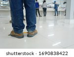 Small photo of Worker stands before the yellow-black line up to wait to buy food in the factory canteen room during corona virus epidemic. (Covid 19)