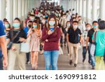 Small photo of Asian woman using mobile phone between Crowd of blurred unrecognizable business people wearing surgical mask for prevent coronavirus Outbreak in rush hour working day at Bangkok transportation