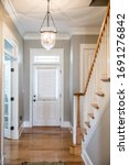 Small photo of View of a white front door entrance in a new construction house with a hanging chandelier clear glass light and a staircasefrom the interior