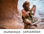 Small photo of Caveman watching the screen of his primitive stone tablet outdoors in a weathered rock cave