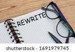 Small photo of the word REWRITE is written in a notebook with glasses