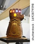 Small photo of Moscow, Russia - April 2020 : Сlose-Up Of Thanos's Infinity Gauntlet. Huge Gold Glove With Infinity Gems. Thanos - Character Of Fortnight Game, Comic And Marvel Movie, Production By Marvel Studio.
