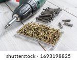 Metal big Screws with screwdriver drill and screwdriver heads (bits) on wooden background. Close up stock photo. - stock photo