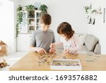 Small photo of Brother and sister playing puzzles at home. Children connecting jigsaw puzzle pieces in a living room table. Kids assembling a jigsaw puzzle. Fun family leisure. Stay at home activity for kids.