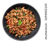 Small photo of Pad Krapow Gai - Thai Basil Chicken in black bowl isolated on white background. Pad Krapow is Thai cuisine dish with minced chicken or pork meat, basil, soy and oyster sauces. Thai Food