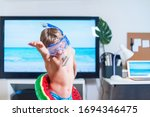 Small photo of Boy in mask and snorkel dive imitating swimming near TV at home. Boy is having fun in mask and floating toy during the quarantine isolation. Stay at home. Play at Home. Coronavirus situation