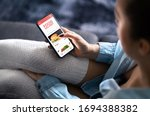 Small photo of Food delivery app in mobile phone. Restaurant order online. Woman using smartphone to get take away lunch home delivered. Fast courier service. Burger menu mock up in cellphone screen.