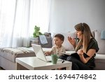 Small photo of Mother working from home with kid. Children make noise and disturb woman at work. Homeschooling and freelance job. Moms Can Balance Work and Family. Multitasking mother working from home.