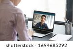 Small photo of Indian girl communicate with friend on-line by video call, pc screen view over female shoulder. Mental health expert online therapy, colleagues work on common project use videoconferencing app concept