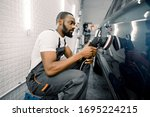 Small photo of Auto detailing service, polishing of the car. Side view of young African American man worker n t-shirt and overalls, polishing blue car door with orbital polisher