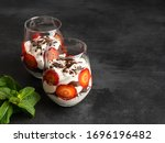 Small photo of Trifle with strawberry, chocolate biscuit and cream cheese mousse. Homemade easy cooking layered dessert served in glass jar and decorated with green fresh mint leaves. Black background, copy space.