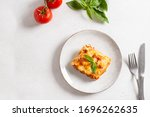 Small photo of Piece of tasty hot lasagna served with a basil leaf on a gray plate. Italian cuisine, menu, recipe. Homemade meat lasagna. Copy space for text, top view