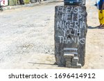 Small photo of Lekki, Lagos / Nigeria - April 7th 2020: Hungry youths leave a sign begging for alms, as things get tougher in Nigeria due to the compulsory lockdown to prevent the spread of coronavirus