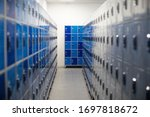 Small photo of Light blue and white metal lockers in a locker room with some doors closed and numbers on doors. Changing dressing room elementary school restroom, security in sport gym. Interior of classic rows lock