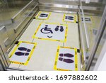 Small photo of View of footprint sign for stand in lift. Social distancing with COVID-19 coronavirus crisis.yellow footprint sign with text caution social distance, Social distancing the elevator (Lift) in hospital.