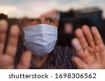 Small photo of Elderly caucasian man wearing hand made protective face mask,in nursing care home,looking outside window, sadness,stress hope in his eyes,self isolation due to global COVID-19 Coronavirus pandemic