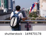 Small photo of BANGKOK-DEC 22: Unidentified Thai people with flag in hand wait to abet the parade of mass people to resist the government of Shinawatra regimes on Dec 22, 2013 in Bangkok, Thailand.
