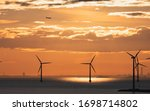 Plane Flying Over Windmills At...