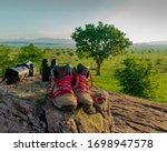 Pair of hiking boots, photography camera and binoculars. Equipment set displayed on a rock after an adventure in the African wilderness. - stock photo