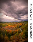 Small photo of Storm clouds approach the High Rollaways in Buckley, MI during the fall color season