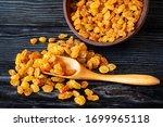Golden Raisins On Black Wooden...