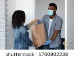 Food delivery during coronavirus. Black courier guy wearing medical mask delivering grocery order to young woman