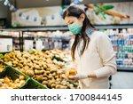 Small photo of Woman with mask safely shopping for groceries amid the coronavirus pandemic in a stocked grocery store.COVID-19 food buying in supermarket.Panic buying,stockpiling.Shortage of fresh produce,vegetables