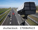Small photo of Security CCTV camera or surveillance system observes vehicular traffic on a road with intentional blur on background