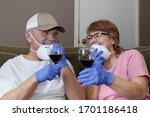 Small photo of horizontal image of a caucasian couple wearing face masks and latex gloves sitting down on the couch for a glass of wine together through a hectic time during the caronavirus pandemic