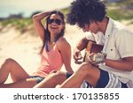 Small photo of Cute hispanic couple playing guitar serenading on beach in love and embrace