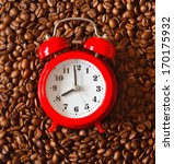 Red alarm clock on a roasted coffee beans background. - stock photo