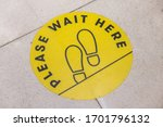 Small photo of footprint sign for stand in shopping mall, supermarket. Social distancing with COVID-19 coronavirus crisis. yellow footprint sign with text caution social distance