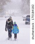 Small photo of Two girls (perhaps sisters) trudge through a snow-covered neighborhood