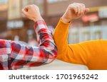 Small photo of Elbow bump. Bump elbows. Friends shaking elbows outdoors. Elbow greeting style. Coronavirus epidemic. Coronavirus, illness, infection, quarantine, COVID-19. Don't shake hands. Stop handshakes.