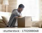 Small photo of Smiling young man sitting on cozy couch at home, unpacking carton box with long-awaited purchased item. Happy male client satisfied with fast delivery service, unboxing order from internet store.