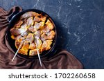 Austrian breakfast torn pancake kaiserschmarrn  with raisins and powdered sugar, cutlery on a black baking dish on a dark concrete background, top view, flat lay, copy space