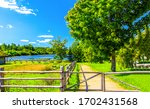 Small photo of Summer farmland fence pathway view. Farm fence in summer scene