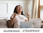 Small photo of Asian young excited woman sit on couch hold notebook on lap feels overjoyed received great news by e-mail message. University admission passed exams scholarship, lottery win, dating invitation concept