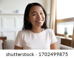 Small photo of Head shot portrait Vietnamese millennial attractive woman sit on couch in living room alone, smiling looking at camera webcam, make video conference call distant interaction using modern tech concept