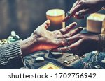Small photo of Fortune teller woman wearing silver rings with turquoise stone and bracelets reads palm lines during fortune telling around candles and other magic accessories. Palmistry and divination