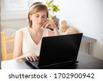 a woman in home clothes works... | Shutterstock . vector #1702900942
