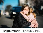 Small photo of Coronavirus. Mom hugs the baby and says goodbye. Woman in a protective mask embrace daughter on the street. Preventive measures against Covid-19 infection. Illness protection. Quarantine.
