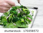 Tossing and serving a healthy green salad with spinach, broccoli and seeds - stock photo