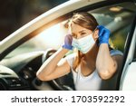 Small photo of A young woman is putting a mask on her face, to avoid infection during flu virus outbreak and coronavirus epidemic, getting ready to go to work by car.